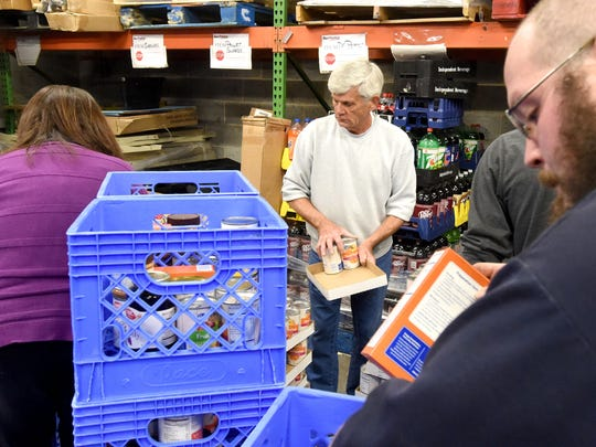 Former Kroger's manager Frank Roetto joins with students from Wilson Memorial, Fort Defiance and Buffalo Gap high schools as well as supermarket employees in packing meal boxes at Kroger's on Arch Avenue in Waynesboro on Tuesday evening, Nov. 22, 2016. The boxes are to be distributed to families in need on Thanksgiving day.