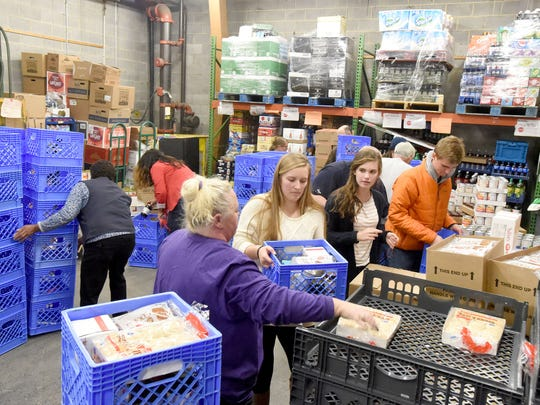 Students from Wilson Memorial, Fort Defiance and Buffalo Gap high schools join with supermarket employees in packing meal boxes at Kroger's on Arch Avenue in Waynesboro on Tuesday evening, Nov. 22, 2016. The boxes are to be distributed to families in need on Thanksgiving day.