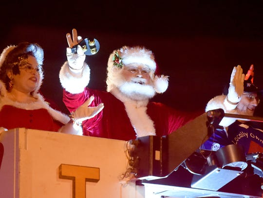 Santa Claus waves to the crowd from on top a fire truck