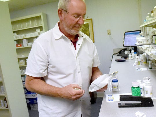 Pharmacist Danny Ray, owner of Ray's Health Mart Pharmacy, bags a medication just filled at the pharmacy in Staunton on Tuesday, Nov. 29, 2016.