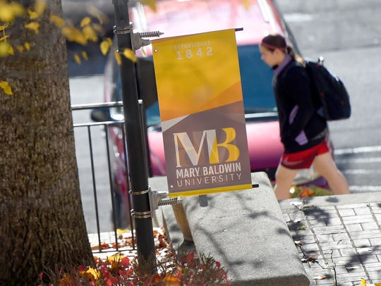A walks past a banner displayed on the campus of Mary