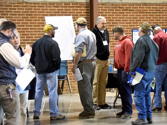 Bryn Smith, an economic development manager with Dominion, stands alongside a map regarding the pipeline construction timeline as he answers questions from those in attendance during an Atlantic Coast Pipeline construction expo held at Augusta Expo in Fishersville on Thursday, Dec. 8, 2016.