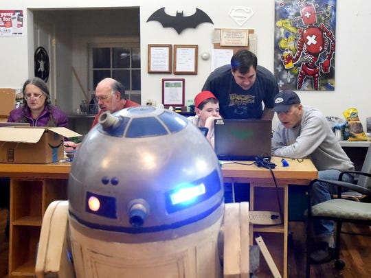 His R2-D2 replica parked nearby, Andy Wiseman assists