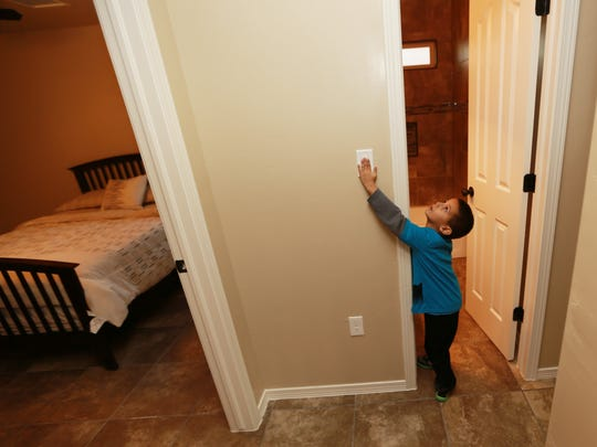 Angel Elias, 5, tried out a light switch in the hallway of his new home Wednesday.