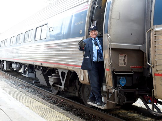 Conductor R.S. Glass offers parting wave as Amtrak's eastbound Cardinal #50 train pulls away from Staunton's train station.