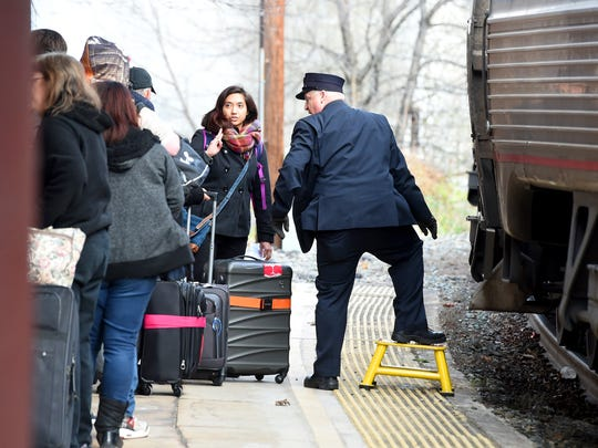 Conductors assist travelers with boarding Amtrak's eastbound Cardinal #50 train before it departs Staunton.