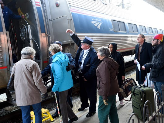 Conductors assist travelers with boarding Amtrak's eastbound Cardinal #50 train before it departs the train station in Staunton.