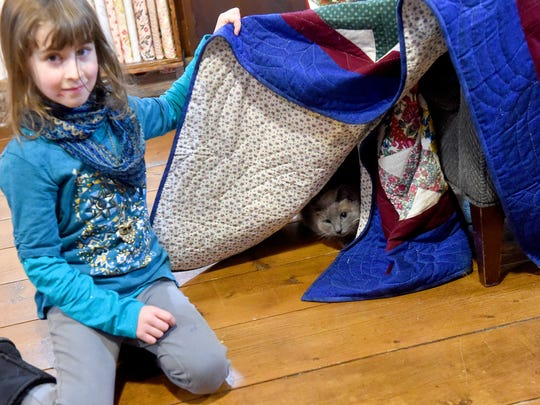Emma Rose Shirey, 7, holds back the quilt to show Sweet