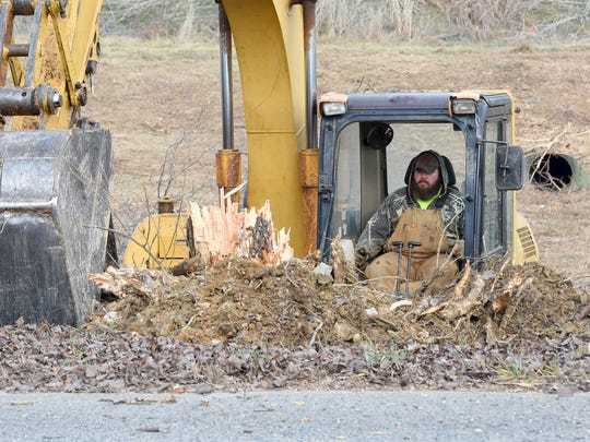 An excavator removes trees from the land designated for Frontier Center project, alongside the road leading towards the entrance to the Frontier Culture Museum Thursday, Jan. 5, 2017.