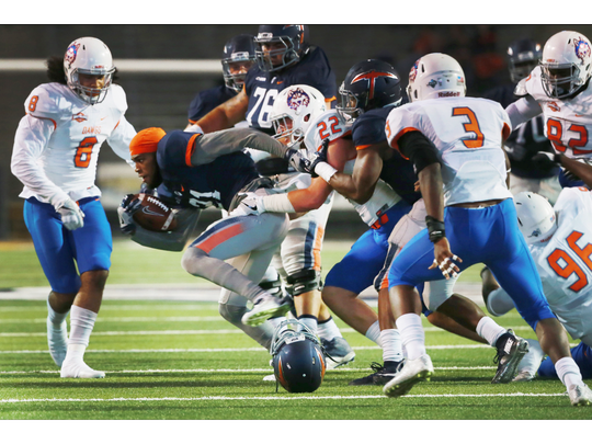 UTEP receiver Eddie Sinegal fights for yardage, minus his helmet, as Houston Baptist defenders work to bring him down during the first quarter Saturday Nov. 5, 2016 in El Paso, Texas. A Houston Baptist player was penalized for grabbing the facemask, which caused the helmet to come off.