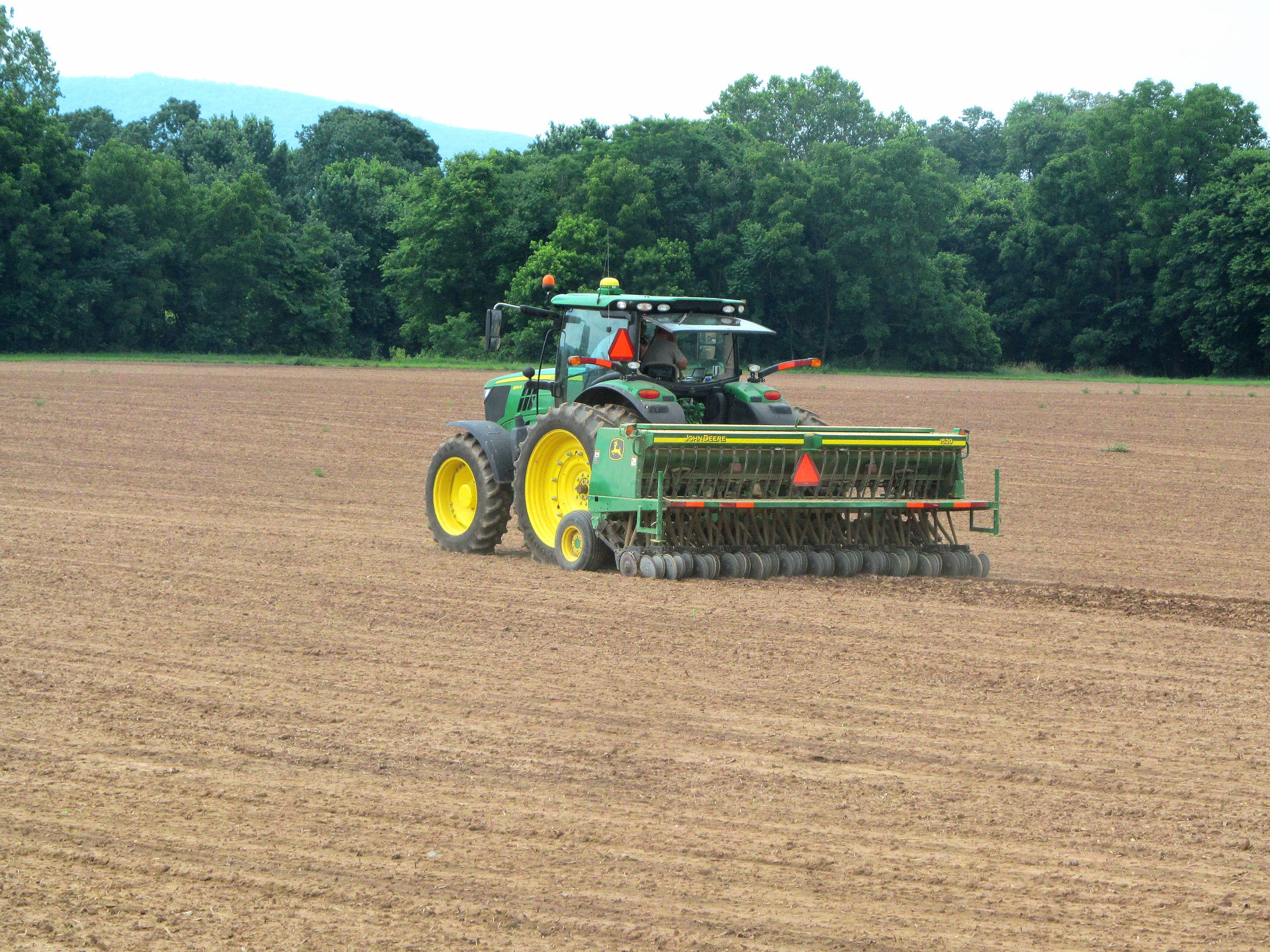A tractor works a field as hemp planting takes place
