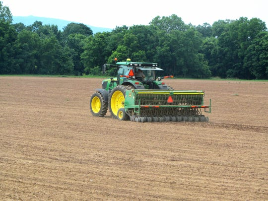 A tractor works a field as hemp planting takes place at Riverhill Farm in Port Republic in 2016.