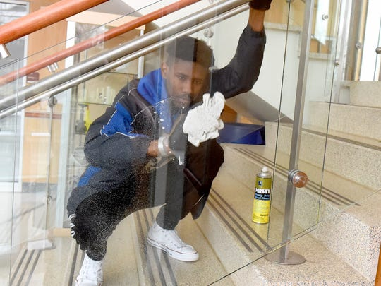 Nyle Buchanan, a student in the college university transfer program, cleans the glass leading up the stairs inside the Advanced Technology Center building.