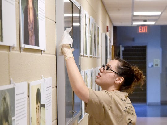 Ashley Kurtz, an administration of justice student, cleans in one of the hallways inside the Fine Arts Center building.