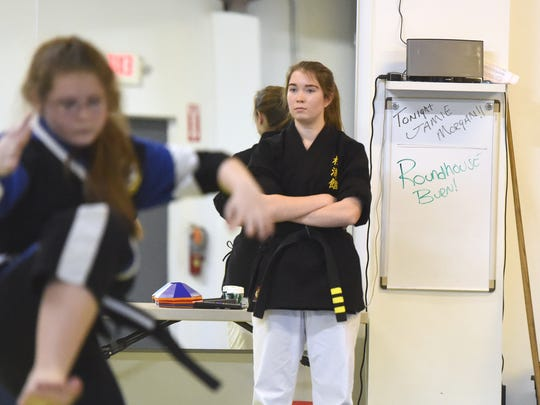 Hannah Dahl, a 3rd degree black belt in American Freestyle Karate, observes as students practice kata, choreographed patterns of movements, as she helps teach during a class at the AFK studio in Staunton on Jan. 12, 2017. Dahl also holds a red belt in Shotokan.