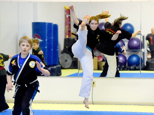 Hannah Dahl, a 3rd degree black belt in American Freestyle Karate, demonstrates a jumping spinning reverse crescent kick to students as she helps teach a class at the AFK studio in Staunton on Jan. 12, 2017. Dahl also holds a red belt in Shotokan.