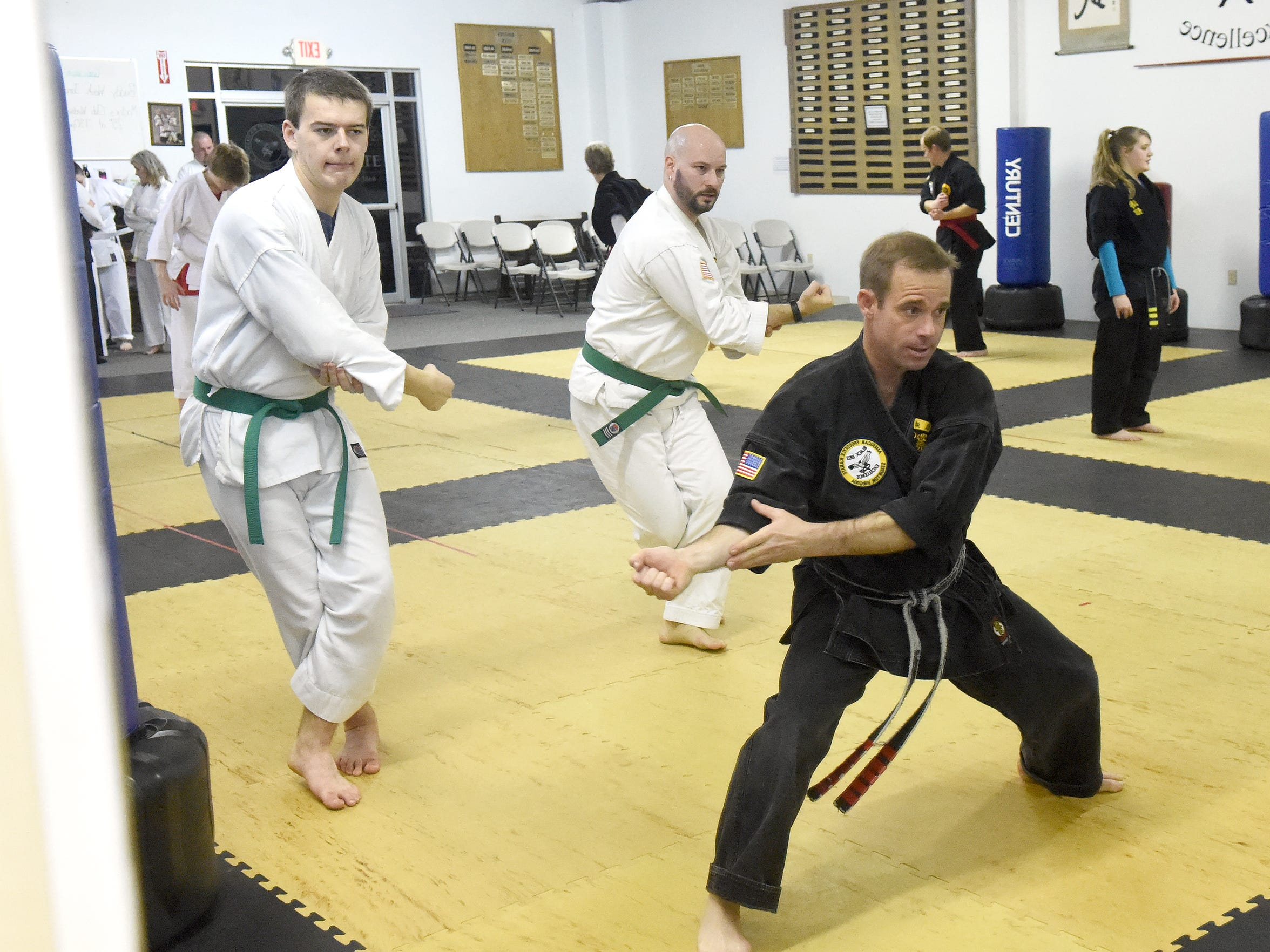 Shotokan green belts Justin Shaw and Jeremy West follow along with John Bowersox, owner of the studio and 3rd degree black belt in Shotokan, as they practice kata during a Shotokan class at the American Freestyle Karate studio in Staunton on Jan. 17, 2017. Bowersox also holds a 5th degree black belt in American Freestyle with West and Shaw holding brown belts.