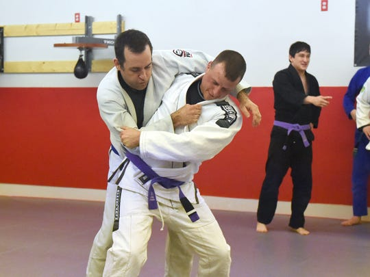 Brian Rose (right), a purple belt in Brazilian jiu-jitsu, performs a hip throw on blue belt Matt Warner during a class at Total Defense Martial Arts in Staunton on Jan. 24, 2017.