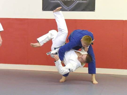 Fifteen-year-old Ryan Benitez (top), a green belt in Brazilian jiu-jitsu, practices hip throws with white belt Dylan Wade as they take turns during a class at Total Defense Martial Arts in Staunton on Jan. 24, 2017.