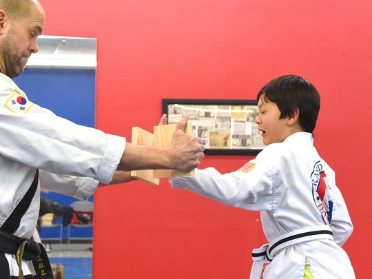 Ten-year-old B.C. Sommerfield, a BoDan (pre-black belt) in Tae Kwon Do, breaks a board held by Master Dan Napier, a 5th degree black belt, during a class at the Dong's Martial Arts studio in Staunton on Feb. 3, 2017.