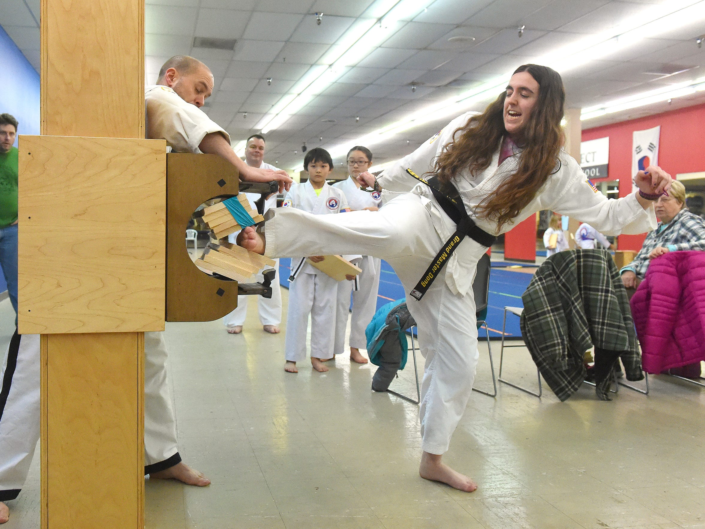 Maggie Rivers, a 2nd degree black belt in Tae Kwon Do, breaks five boards with a side kick during a class at the Dong's Martial Arts studio in Staunton on Feb. 3, 2017.