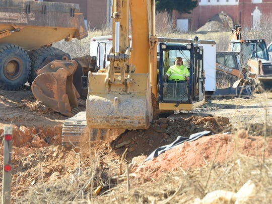 An excavator works to move earth and load dump trucks. Construction continues on land designated for the Frontier Center project, alongside the road that leads to the entrance of the Frontier Culture Museum in Staunton on Monday, Feb. 20, 2017.