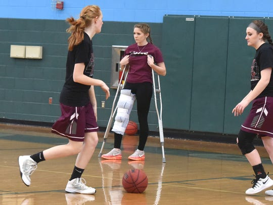 Despite a leg injury, Stuarts Draft's Deborah Black stays with her teammates as they warm up before their game against George Mason High School during a Region 2A East girls consolation game played in Mechanicsville on Saturday, Feb. 25, 2017.
