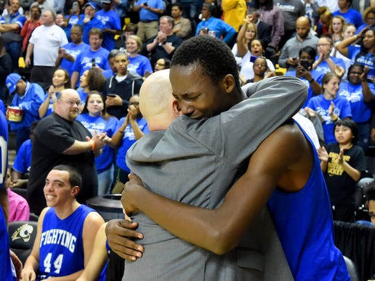 Robert E. Lee's Darius George hugs head coach Jarrett Hatcher as they celebrate their victory over Amelia High School to win the Group 2A state championship in Richmond on Thursday, March 9, 2017.