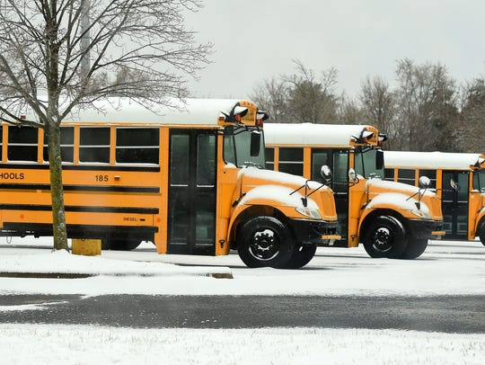 School buses are parked in the snow in the Kmart parking