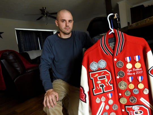 Ryan Rathburn wears his varsity letter jacket, earned while at Riverheads High School, at his home on Monday, March 20, 2017. He suffered three concussions while playing football at the school. One occurred playing junior varsity football in 2003 with a second during a varsity game in 2005 and a third in practice that same year.
