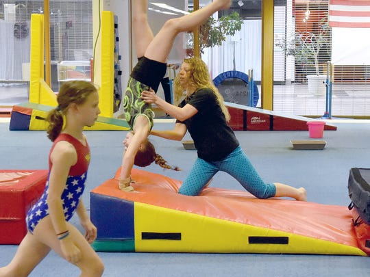 Head coach Kristen Hamlin works with members of the competition team at Head Over Heels Gymnastics on Wednesday, April 4, 2017. Hamlin and others have worked to keep the business going after former owner, Stacey DeHaven, died in a car wreck in October.