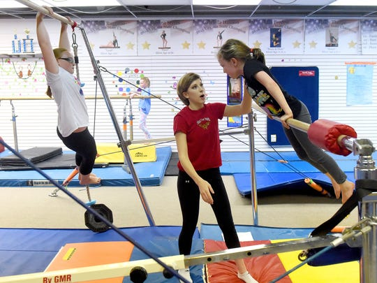 Coach Sarah Beverage works with students in the intermediate 1 and 2 classes at Head Over Heels Gymnastics on Wednesday, April 4, 2017. Beverage and others have worked to keep the business going after former owner, Stacey DeHaven, died in a car wreck in October.