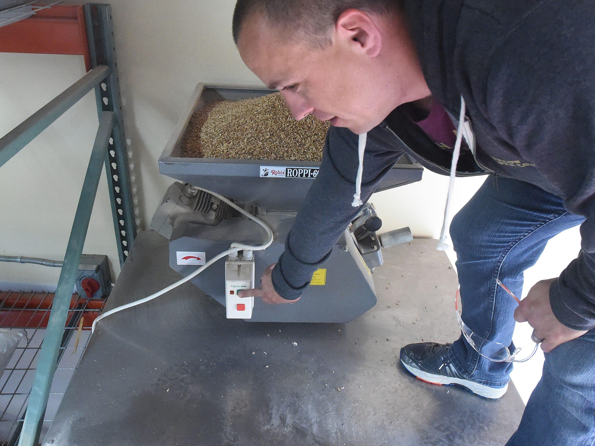 Owner Aaron Allen grinds grain for use in brewing,