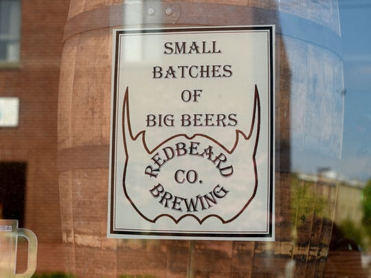 "A sign in the window of Redbeard Brewing Company says their slogan, ""Small batches of big beers."""