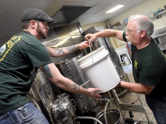 Alan Smith, a cellarman, receives another bucket of grain to pour into the mash tun from owner Mike Chappel waits with the next bucket of grain mixture. They begin brewing another batch of Shenandoah Pale Ale at Shenandoah Valley Brewing Company on April 14, 2017.