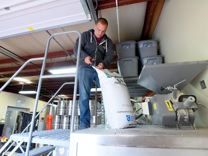 Owner Aaron Allen opens another bag of grain to be