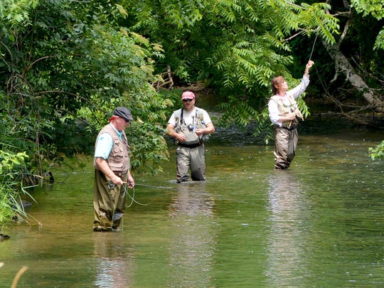Standing in the South River, instructor Tommy Lawhorne (center) of South River Fly Shop teaches Rick and Justine Bartow of Culpeper the art of fly fishing in Waynesboro in June 2014.