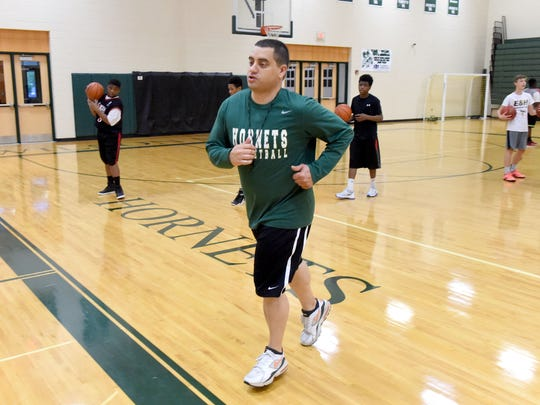Coach Jeremy Hartman jogs off the court to reset the clock. He works with young basketball players practicing their skills during an open gym at Wilson Memorial High School on April 27, 2017. It was recently announced that Hartman will be taking over as head coach of the school's boys varsity basketball team.