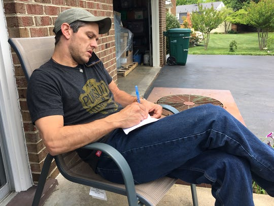 Adam Stanley, owner of Stanimal's 328 Hostel in Waynesboro, talks on the telephone with a hiker who will be coming through the area later this month and needs a place to stay.