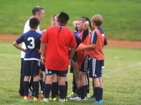 Coach Jeff Alger talks with his players during the Rockbridge Augusta U12 soccer practice Thursday night at the Weyers Cave Community Center.
