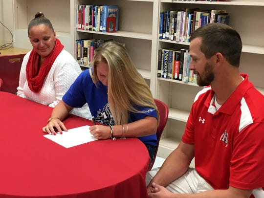 Riverheads senior Madison Cash, center, will play softball for Eastern Mennonite University next year. With her mom, Misty Cash, and high school coach, Chad Coffey, watching, Madison signed her celebratory form EMU on Tuesday afternoon in Riverheads' library.