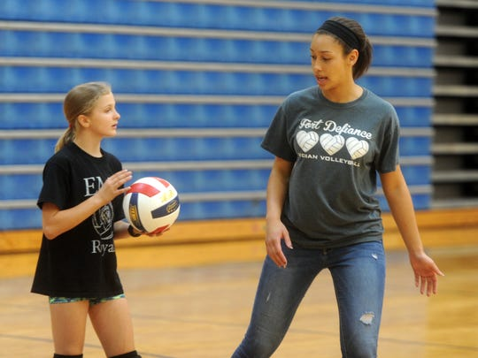 Maecy Ann Frizzelle, left, listens to advice from Fort Defiance senior Jayden Beasley during volleyball camp at Fort on Tuesday morning.