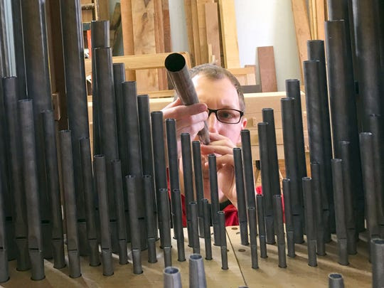 Aaron Reichert checks the voicing of the pipes to the organ on Feb. 9, 2017.
