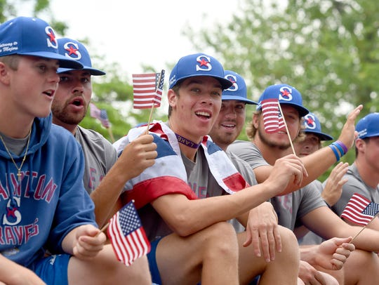 The Staunton Braves baseball team wave flags as they