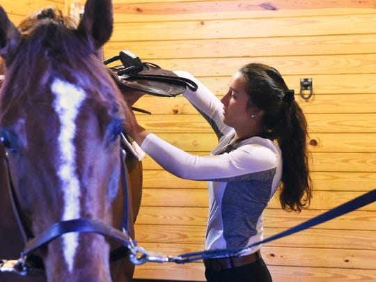 MacKensie Bowles, 17, of Staunton saddles Chewy, a Zangersheide Warmblood, before riding him in Staunton on Wednesday, July 5, 2017. Bowles, who also plays volleyball for Robert E. Lee High School, will be competing in the US junior hunter national championship later this month.