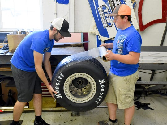 Team manager and crew chief Trevor Cash and driver Logan Roberson work together at prepping a tire for the next race. They work in a shop in Waynesboro on Wednesday, July 19, 2017.