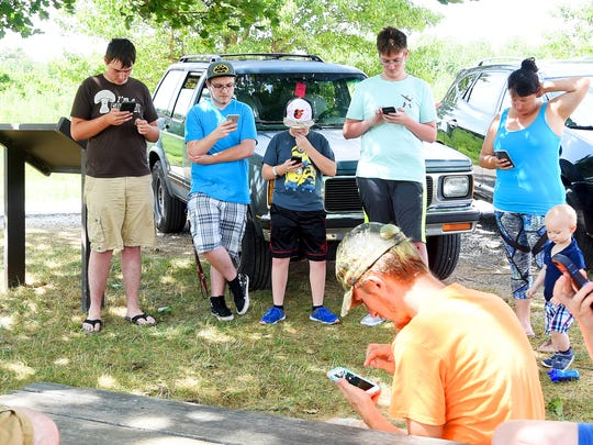 Some of the members of a group of 20 random Pokemon GO players gather around a historical interpretive sign for the Barger House along the road leading to the entrance of the Frontier Culture Museum. Together, they use the game app on smart phones and tablets to battle a legendary Pokemon named Lugia on Monday, July 24, 2017. If successful, each receives the chance at attempting to capture Lugia for their personal game.