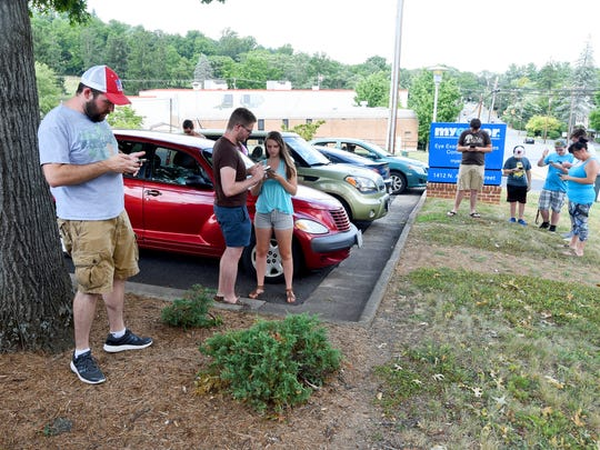 A group of 20 random Pokemon GO players have gathered near the metal sculpture of reading glasses on North Augusta Avenue. They work together, using the game app on smart phones and tablets, to battle a legendary Pokemon named Lugia on Monday, July 24, 2017. If successful, each receives the chance at attempting to capture Lugia for their personal game.
