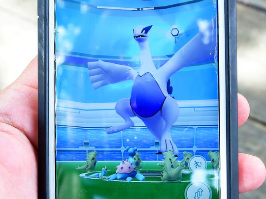 The raid battle against Lugia, a rare legendary pokemon, is viewed through the Pokemon GO game app. The creature battles up to 20 random players gathered at the historical interpretive sign for the Barger House along the road leading to the entrance of the Frontier Culture Museum on Monday, July 24, 2017.