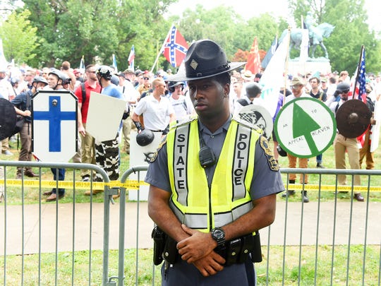 A Virginia State Police officer stands on the perimeter of Emancipation Park fenced off for a white supremacist rally.
